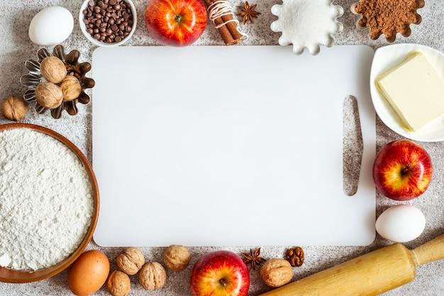 Tábua de corte vazia e ingredientes para assar com maçãs e especiarias.