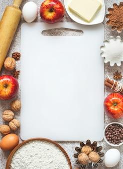 Tábua de corte vazia e ingredientes para outono e inverno, assando com maçãs e especiarias.