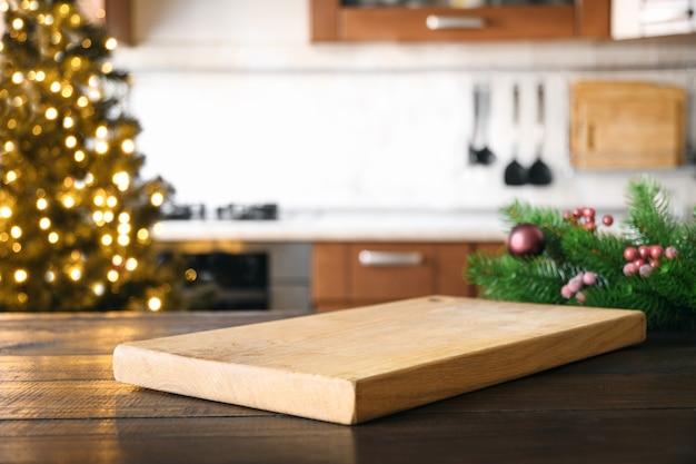 Tábua de corte vazia na mesa de madeira com cozinha turva de férias