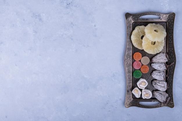 Tábua de lanche metálica com frutas secas e marmeladas