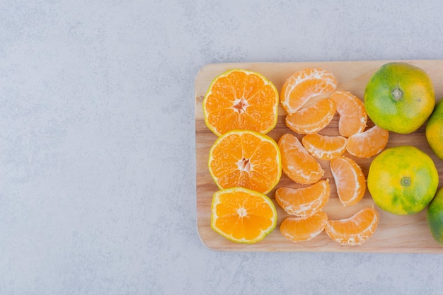 Tábua de madeira cheia de tangerinas ácidas em fundo branco. foto de alta qualidade