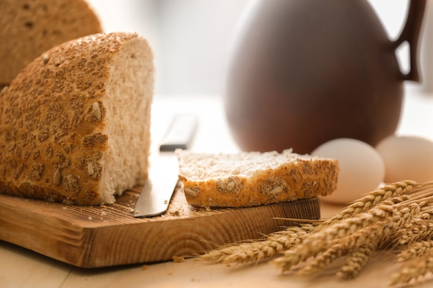 Tábua de madeira com corte de pão e faca na mesa da cozinha