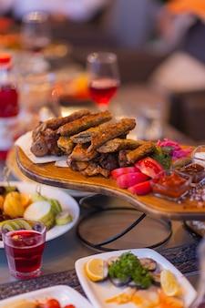 Tábua de madeira com costela de porco assada quente e linguiça, decorada com manjerona fresca.