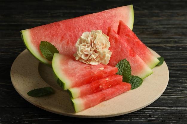 Tábua de madeira com fatias de melancia, folhas de hortelã e flores Foto Premium