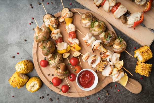 Tábua de madeira com frango grelhado e espetos de legumes na mesa