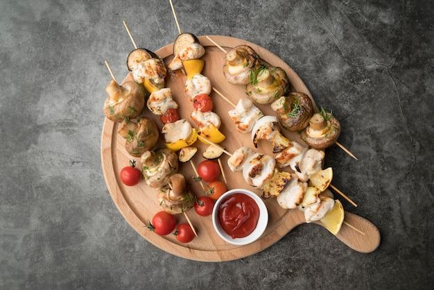 Tábua de madeira com frango grelhado e espetos de legumes