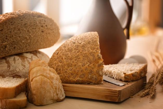 Tábua de madeira com pão cortado na mesa da cozinha