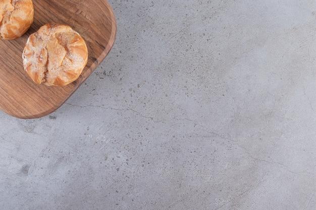 Tábua de madeira com profiteroles doces com chantilly na superfície da pedra