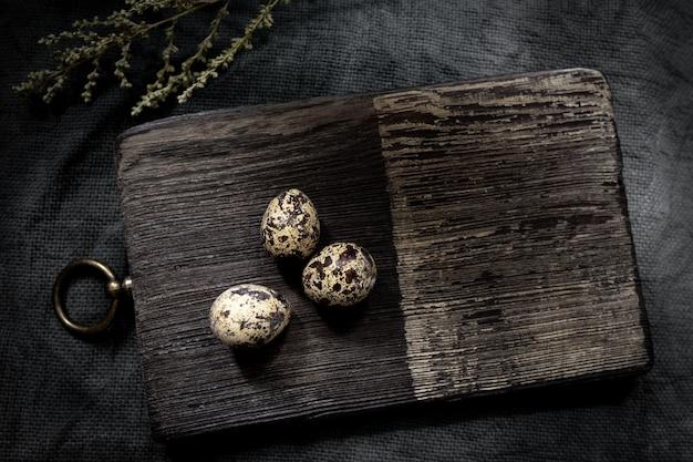 Tábua de madeira com três ovos de codorna