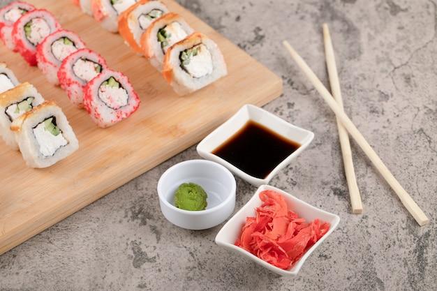 Tábua de madeira com vários rolos de sushi com gengibre e molho de soja na mesa de mármore