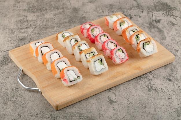 Tábua de madeira com vários rolos de sushi na mesa de mármore