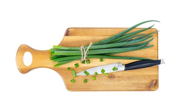Tábua de madeira da cozinha para cortar cebolas verdes frescas.