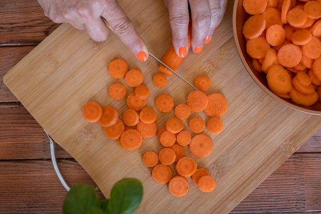 Tábua de madeira e mãos femininas cortando cenouras frescas em forma redonda - saudável, dieta, conceito de vegetais