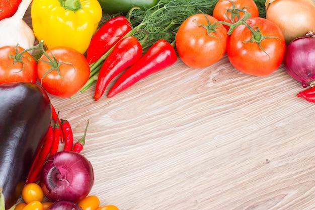 Tábua de madeira em branco com vegetais coloridos Foto Premium