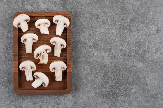 Tábua de madeira fatiada de cogumelo orgânico sobre superfície cinza