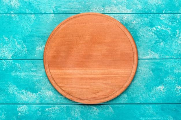 Tábua de madeira redonda para pizza na mesa de madeira azul. maquete para projeto de alimentos. vista do topo.