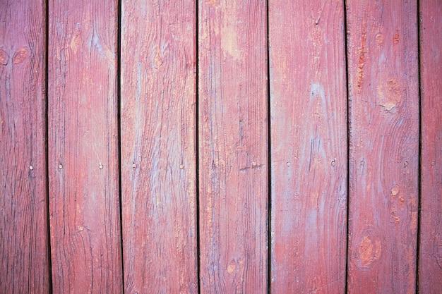 Tábua de madeira rústica rosa, com rachaduras e fundo de madeira natural