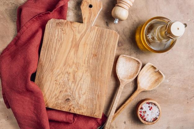 Tábua de madeira sobre a toalha com os utensílios na mesa da cozinha rústica.