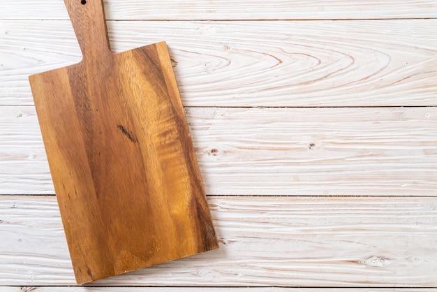 Tábua de madeira vazia com pano de cozinha em fundo de madeira, vista superior