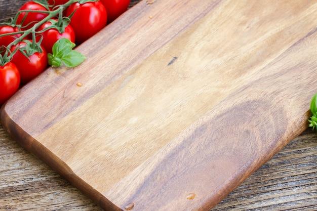 Tábua de madeira vazia com tomate cereja vermelho