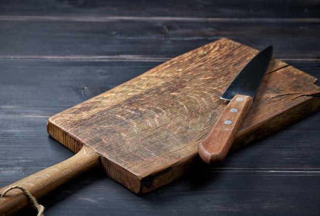 Tábua de madeira vazia e faca na mesa da cozinha rústica