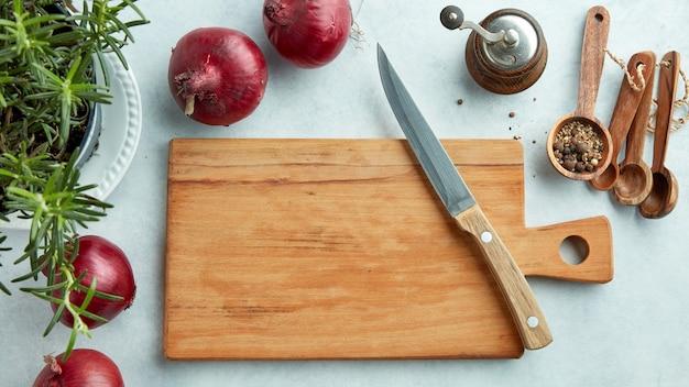 Tábua de madeira vazia e faca na mesa da cozinha, vista superior