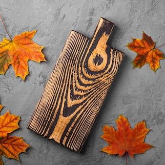 Tábua de madeira velha artesanal com folhas de outono no fundo de concreto, vista superior