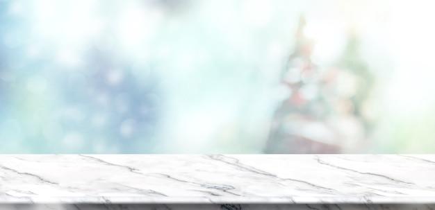 Tábua de mesa de mármore branco vazia com árvore de natal borrada e borrão abstrato e fundo de queda de neve com luz bokeh