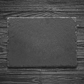 Tábua de pedra vazia sobre uma mesa de madeira. conceito: cozinha, culinária, restaurante, menu