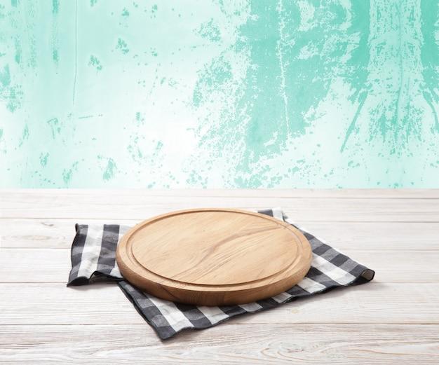 Tábua de pizza vazia e toalha de mesa em deck de madeira