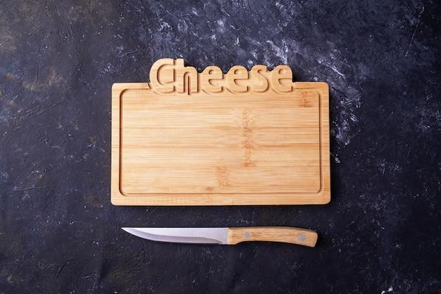 Tábua de queijo de madeira vazia uma faca. vista do topo.