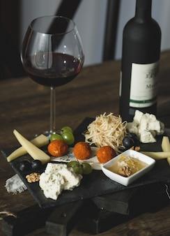 Tábua de queijos com bolinhas de queijo e um copo de vinho
