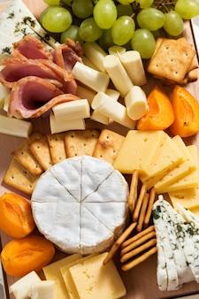 Tábua de queijos com frutas, carne e biscoitos.