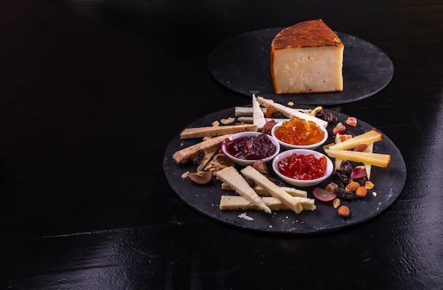 Tábua de queijos com nozes e geleias em um fundo de ardósia preta.