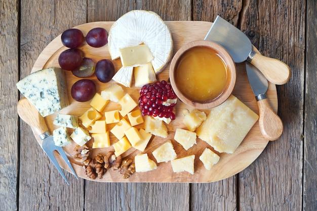 Tábua de queijos com queijo camembert, queijo parmesão, queijo maasdam. a composição é complementada por mel em prato de madeira, uvas e nozes. facas especiais estão por perto. vista do topo.