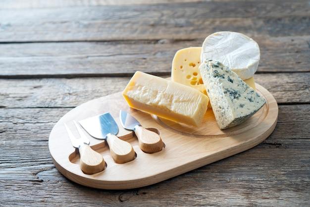 Tábua de queijos com queijo camembert, queijo parmesão, queijo maasdam. fundo de comida rústica.
