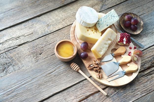 Tábua de queijos com queijo camembert, queijo parmesão, queijo maasdam. vista superior, copie o espaço.
