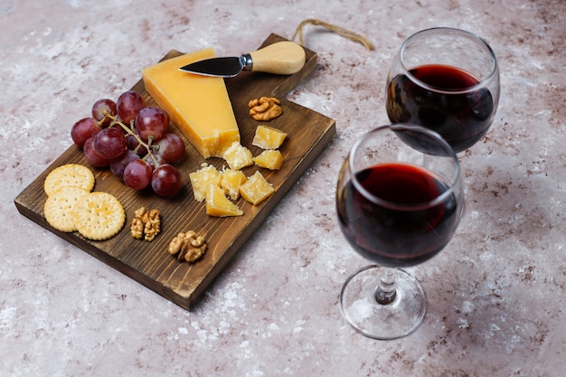Tábua de queijos com queijo duro, faca de queijo, copo de vinho tinto, uva na superfície de concreto marrom