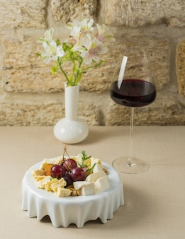 Tábua de queijos com um copo de vinho tinto francês