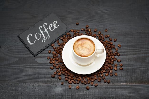 Tábua de servir de pedra com sinal manuscrito de giz xícara de café expresso e grãos de café na mesa de madeira escura