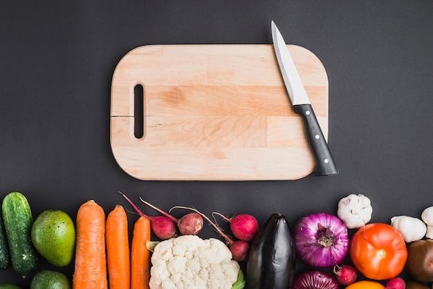 Tábua e faca perto de legumes