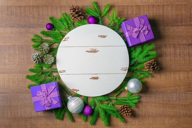 Tábua redonda branca e decoração de natal em fundo de madeira