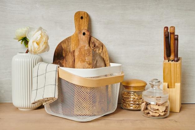 Tábuas de cortar de madeira em um balde branco com outros objetos ao lado