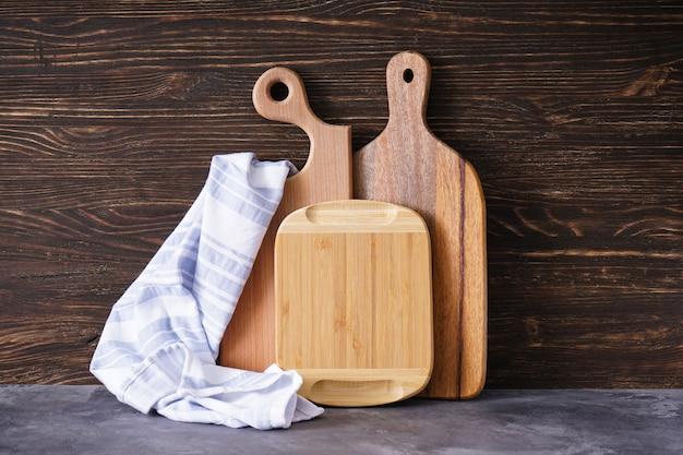 Tábuas de corte de madeira e toalha de cozinha na mesa de madeira