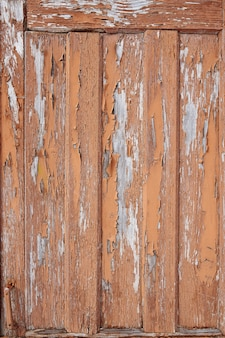 Tábuas de galpão de madeira velhas com pintura descascada.