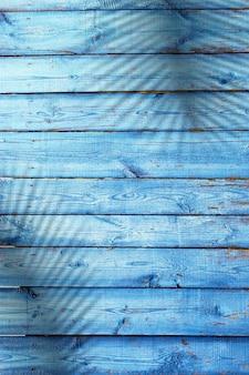 Tábuas de madeira azuis naturais com sombras de folhas de palmeira, fundo de textura de madeira
