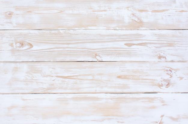 Tábuas de madeira clara pintadas de branco com arranhões de tinta