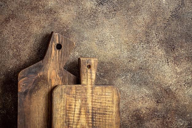 Tábuas de madeira de cozinha antigas em mesa de madeira marrom