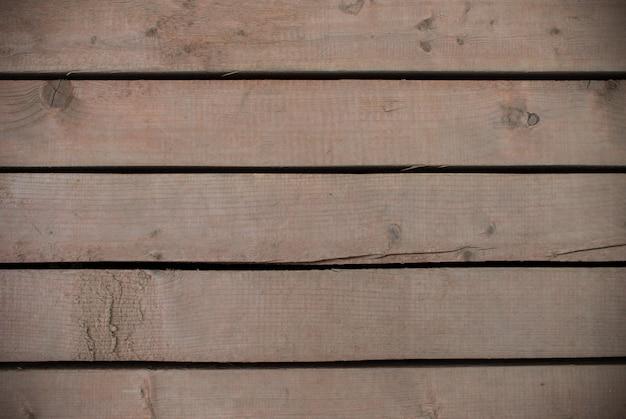Tábuas de madeira marrom com textura de furos entre elas. espaço para design
