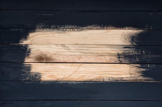 Tábuas de madeira não totalmente pintadas de preto. lugar para texto. trabalho em progresso